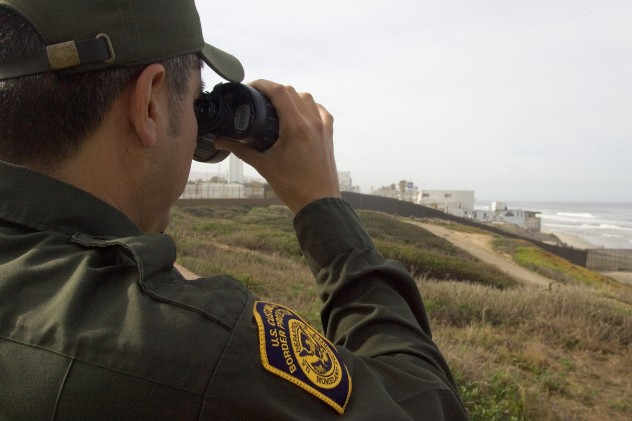 CBP agent watches people as they gather next to the Mexican/American border in Imperial Valley CA.