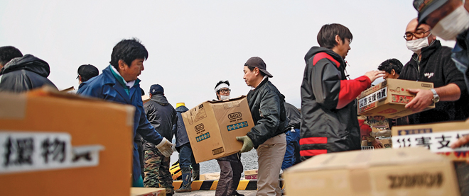 People unload aid from a small ship at the devastated port of the island of Oshima