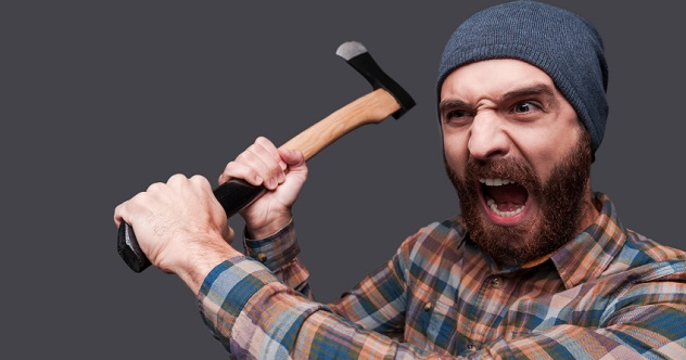 Furious lumberjack. Furious young bearded man swinging his axe and shouting while standing against grey background
