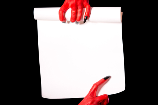 Red devil hands holding paper scroll