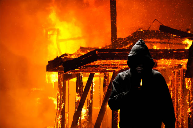 Hooded person holding a lighter in front of burning house