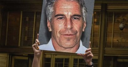 Protestor holding Jeffrey Epstein poster